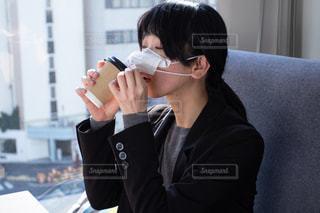 マスクを外してコーヒーを飲む女性の写真・画像素材[3299117]