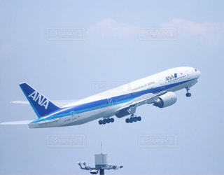 青い空を飛ぶ大型旅客機の写真・画像素材[933564]