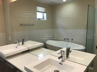 洗面台と鏡付きのバスルームの写真・画像素材[883586]