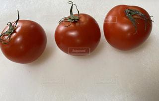テーブルの上に座っている赤いリンゴの写真・画像素材[2869166]