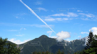 山の飛行機雲の写真・画像素材[953534]