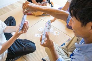 自分の携帯電話を見てテーブルに座っている人々 のグループの写真・画像素材[1320284]