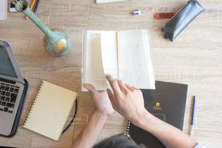 ノート パソコンでテーブルに座っている人の写真・画像素材[1323123]