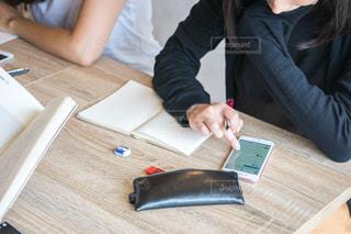 ラップトップを使用してテーブルに座っている女性の写真・画像素材[1323125]