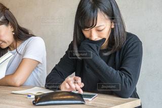 テーブルに座っている女性 スマホの写真・画像素材[1323128]
