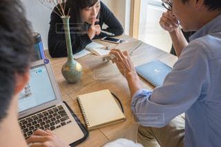 ノート パソコンを見てテーブルに座っている人々 のグループの写真・画像素材[1323188]