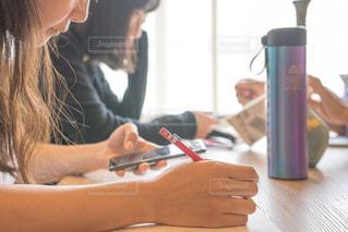 テーブルに座っている女性 カフェ 勉強の写真・画像素材[1323193]