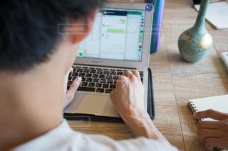 テーブルの上に座っているラップトップ コンピューターを使用している人 カフェ勉強の写真・画像素材[1323206]