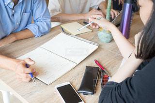 ラップトップを使用してテーブルに座っている人の写真・画像素材[1323207]