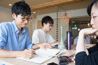 男とラップトップを使用してテーブルに座っている女性の写真・画像素材[1323209]