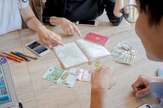 ラップトップを使用してテーブルに座っている人 海外 旅行計画の写真・画像素材[1339757]