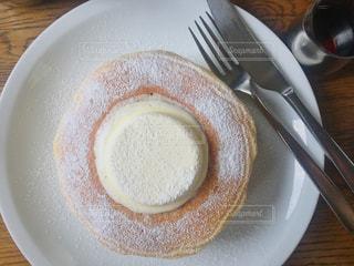 ナイフとフォークの白い皿の上のケーキの一部 パンケーキの写真・画像素材[1354013]
