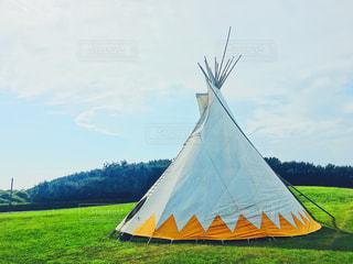 大きな白い建物の芝生のフィールドでテントのティピの写真・画像素材[1434742]