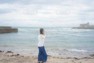 砂浜の上に立っている女性の写真・画像素材[1457194]