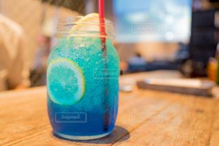 テーブルに座っている青いボトルとガラス 青色の飲み物を飲むの写真・画像素材[1467596]