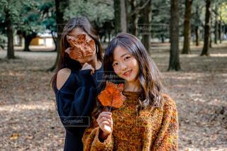 落ち葉を持っている二人の女性の写真・画像素材[1594946]