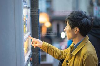 自動販売機の前に立つ男性の写真・画像素材[1846785]