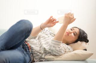 ベッドの上で横になって携帯をいじる女性の写真・画像素材[1846819]