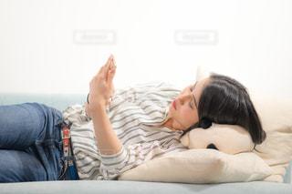 ベッドの上で横になってスマートフォンをいじる女子の写真・画像素材[1846820]
