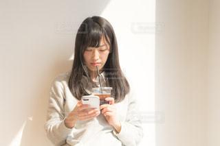携帯電話を持ってコーヒーを飲む人の写真・画像素材[2097798]