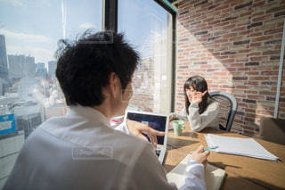 窓の前のテーブルに座っている人達の写真・画像素材[2097810]