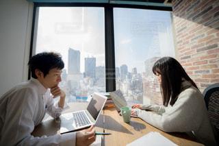 ラップトップコンピュータを使ってテーブルに座っている男性と女性の写真・画像素材[2097811]