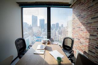窓の横にあるテーブルの上に座っているラップトップコンピューターの写真・画像素材[2097816]