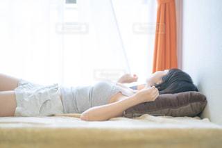 ベットの上で寝転がる女性の写真・画像素材[2235193]