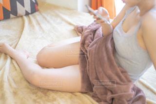 ベットの上で携帯電話をいじる女性の写真・画像素材[2235211]