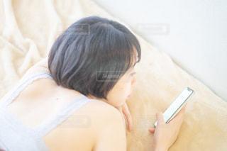 ベットの上で携帯電話をいじる女性の写真・画像素材[2235216]