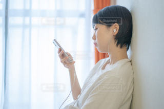 ベットの上で音楽を聴く女性の写真・画像素材[2235237]