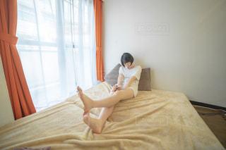 ベットの上でくつろぐ女性の写真・画像素材[2235313]