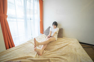 ベットの上に座る女性の写真・画像素材[2235315]