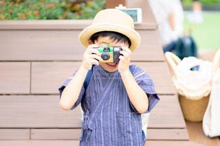 帽子をかぶってカメラを構える男の子の写真・画像素材[2312509]