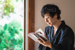 縁側で本を読む男性の写真・画像素材[2413917]