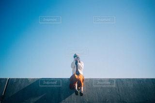 防波堤に座る女の子の写真・画像素材[2751834]