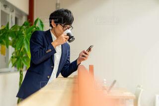 コーヒーを飲みながらスマホをいじる人の写真・画像素材[2910316]