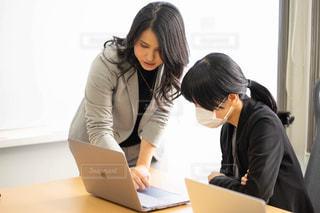 ラップトップを見て机に座っている女性の写真・画像素材[2972377]