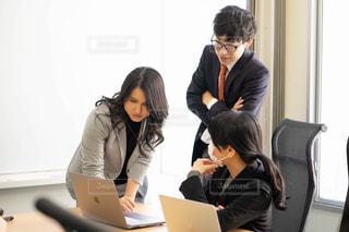 ラップトップを見て机に座っている男と女の写真・画像素材[2972402]