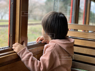 窓の前のベンチに座っている少女の写真・画像素材[3067017]