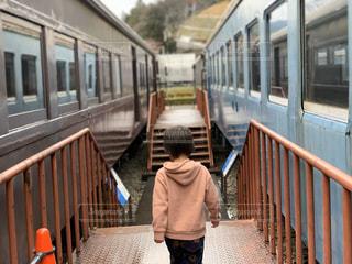 電車の隣に立っている少年の写真・画像素材[3067016]