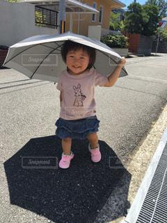 傘をさしている小さな女の子の写真・画像素材[1450645]