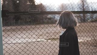 フェンスの前に立っている人の写真・画像素材[1686721]