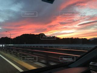 背景の夕日と高速道路の写真・画像素材[972416]