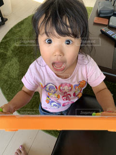 テーブルの上に座っている小さな女の子の写真・画像素材[2303804]
