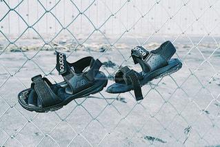 フェンスの横にある靴のグループの写真・画像素材[754267]