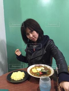 食品のプレートをテーブルに座っている女性の写真・画像素材[1715275]