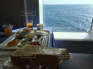 水のガラスの横のテーブルの上に座ってサンドイッチ - No.714876