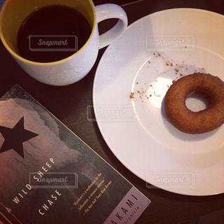 一杯のコーヒーとドーナツと洋書の写真・画像素材[1409616]