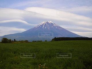 背景の山に大規模なグリーン フィールドの写真・画像素材[1194448]